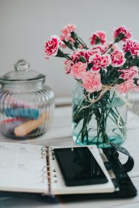 Kaboompics - Organizer, mobile phone and lovely pink flowers