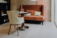 Table between chair and orange sofa in floral living room or restaurant