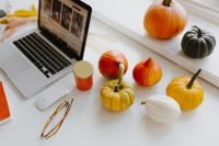 Female desk with orange notebook and pumpkins
