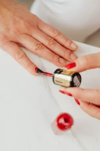 Kaboompics - Closeup of a woman painting her nails with red nail polish
