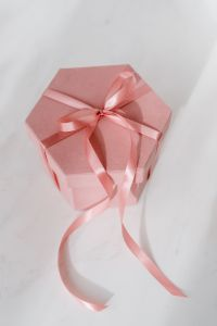 Kaboompics - Light pink velvety box with satin ribbon on white marble