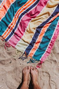 Kaboompics - Womans' feet and colorful beach towel on the sand