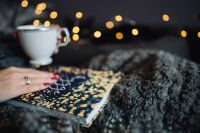 Kaboompics - Young woman at home reading Hygge book and drinking coffee or tea