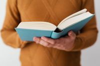 Kaboompics - A man in a brown sweater reading a book, white background