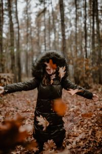 Kaboompics - A woman throws up the autumn brown leaves