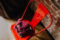 Kaboompics - Industrial red metal chair with a bouquet of pink flowers and books on it