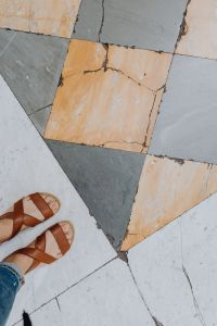 Kaboompics - A woman wearing blue jeans and leather sandals stands on a marble, natural stone floor