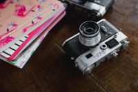Kaboompics - Old analog cameras and pink books on a wooden table