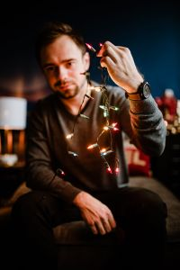 A handsome young man with Christmas tree lamps