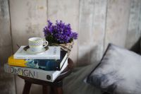 Books, purple flowers and a white cup on a wooden stool by the bed