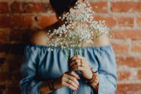 Kaboompics - A woman in a blue dress holds a branch of Baby's Breath flower