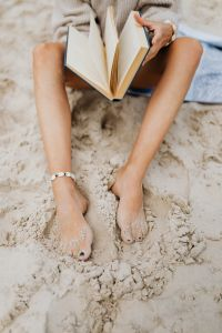 Kaboompics - A woman reads on the beach in the summer