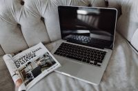 Silver Apple MacBook Pro with a magazine on a bed