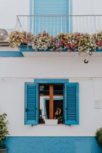White building with blue shutters and flowers on the balcony