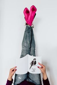 Kaboompics - A woman in pink boots and blue jeans reads a book