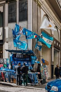 Stall with gadgets for fans of the football club SSC Napoli, blue flags and T-shirts