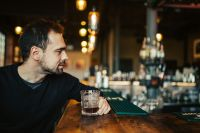 Kaboompics - Handsome young man having a whiskey in a pub