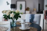 Round breakfast table with golden coffee mats and white flowers