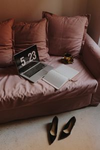 Kaboompics - Workplace with a laptop, organizer, high heels shoes and coffee on a pink couch