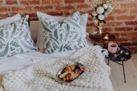 Croissants and figs on a green plate, a cup of coffee and a candle