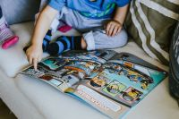 Kaboompics - Child reading a comic story