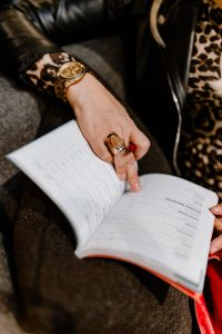 Kaboompics - A woman with a large ring and a golden watch writes down in the calendar