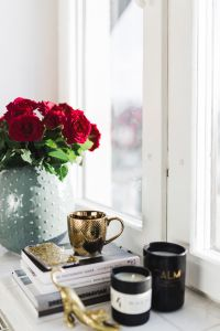 Gold cup of coffee and red roses bouqet
