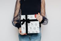 Woman in Black Blouse Holds a Christmas Gift