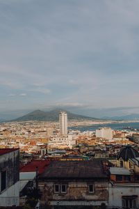 Panorama of the city Naples and the volcano Vesuvius. Old houses at sunset