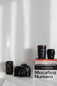 Photographer's desk - books, DSLR camera and lenses