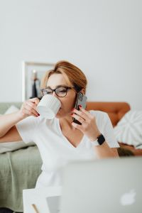Woman drinks coffee - talking on the mobile phone