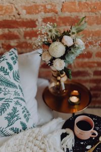 A bouquet of flowers and a cup of coffee on the bedside table