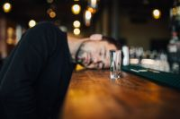 Drunk and unconscious man lying on a counter in a classy bar