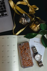 Home office desk with Macbook, iPhone, calendar, watch & organizer