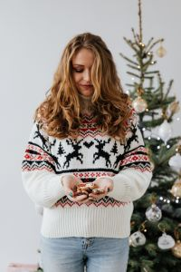 The woman in the Christmas sweater holds gingerbread