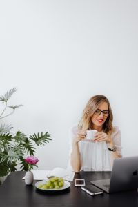 Kaboompics - A businesswoman drinks coffee in the office at her desk