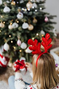 Kaboompics - Woman Wearing Reindeer Horns on Head, Wrapping Gift, Christmas Tree Background