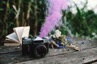 Kaboompics - Colorful smoke bomb, book and vintage camera