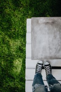Kaboompics - Concrete side table and green grass in garden, woman, jeans, sneakers