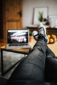 Woman in ripped jeans and black sneakers with a silver laptop on a wooden table