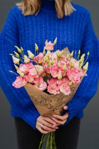 Close up of woman holding bouquet of pink lisianthus flowers wrapped in brown paper