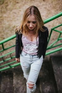 Blonde woman in a black jacket and ripped jeans by a green handrail