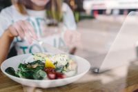 Kaboompics - Close up image of young woman eating classic breakfast at restaurant