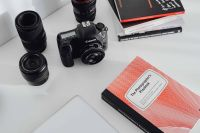 Kaboompics - Photographer's desk - books, DSLR camera and lenses