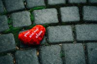 Small red heart on a cobblestone path