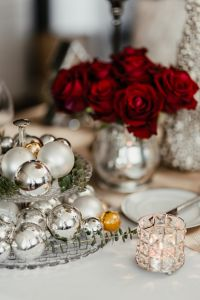 Kaboompics - Silver Christmas tree balls on the stand, candle holder and red roses in a silver vase on the table