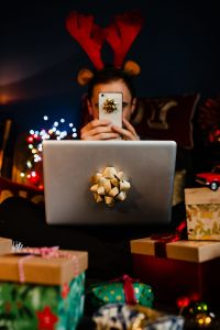 Kaboompics - A handsome man with Christmas presents - using mobile phone & MacBook laptop