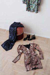 Kaboompics - colored sequin dresses and boots lie on a wooden parquet