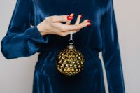 Woman in Blue Blouse Holds a Christmas Tree Bauble