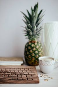 Wooden keyboard, cup of coffee, pineapple and golden jewellery